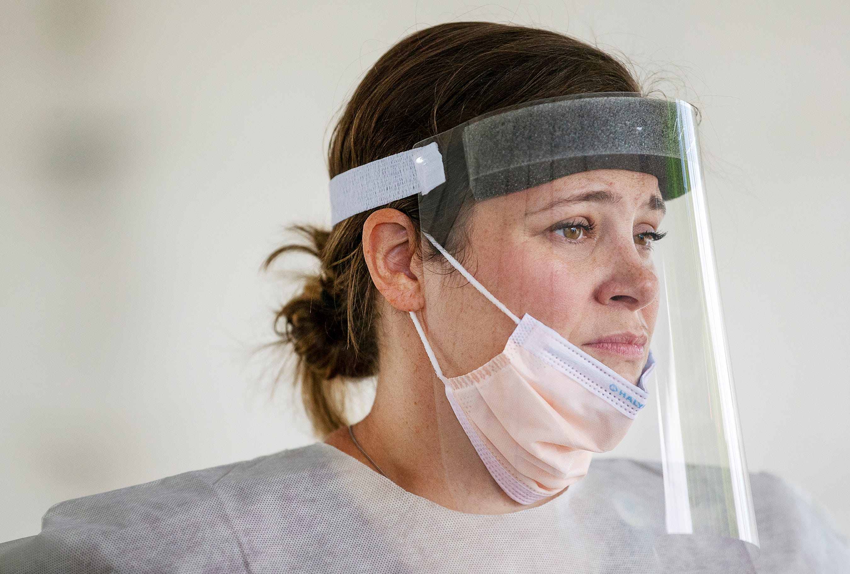 """After comforting a woman she swabbed for COVID-19 testing, registered nurse Jenna Puckett takes a momentary rest before resuming testing at a mobile site in Cape Coral, Fla. """"She was afraid and overwhelmed,"""" Puckett said of the woman she tested. """"She just needed someone to listen."""""""