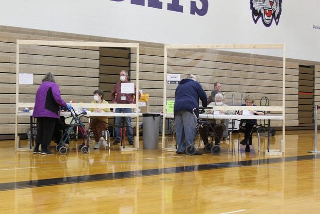 Voters get ballots from poll workers at Green Bay West High School during the April election. There is a shortage of poll workers for the Nov. 3 general election.