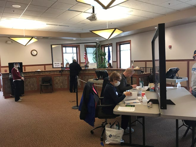 A number of people wear face masks Tuesday during spring primary voting at Allouez Village Hall.