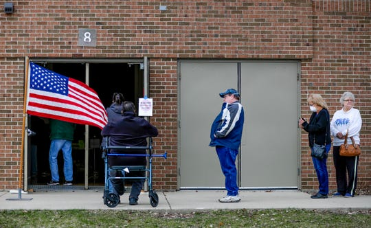 Voters waited in line  at Green Bay West High School for up to four hours Tuesday. The city of Green Bay reduced the number of polling places from 31 to two because of the coronavirus pandemic.