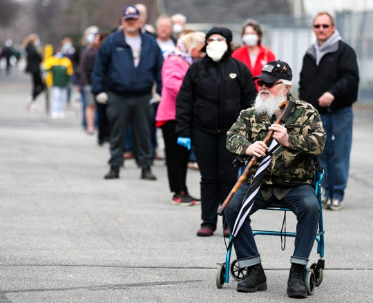 Gene Wheaton sits on his walker while waiting in line to vote on Tuesday at Green Bay West High School.