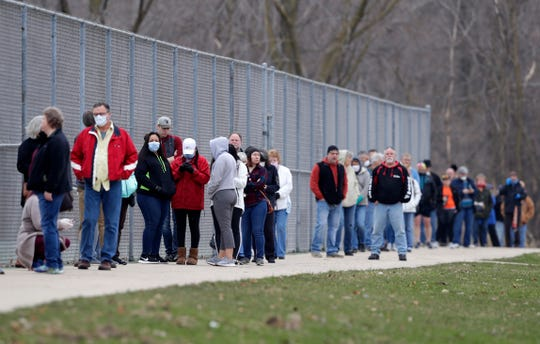 Voters, many of whom wore masks or other face protection, wait in line April 7, 2020, outside Green Bay East High School, one of two polling locations for Green Bay residents.