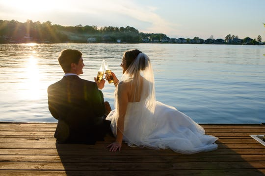 Jennifer Coffey and Robert Arcovio drink Coronas after getting married at Lake Murray in South Carolina on April 4, 2020.
