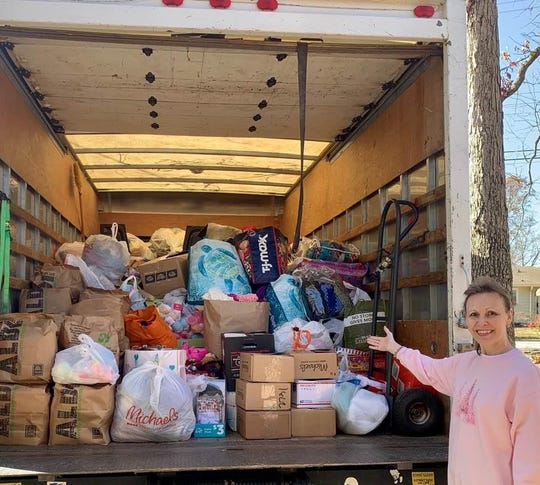 """Debbie Addis stands near a truck load of Christmas gifts her program, """" With These Hands,"""" collected for the less fortunate."""