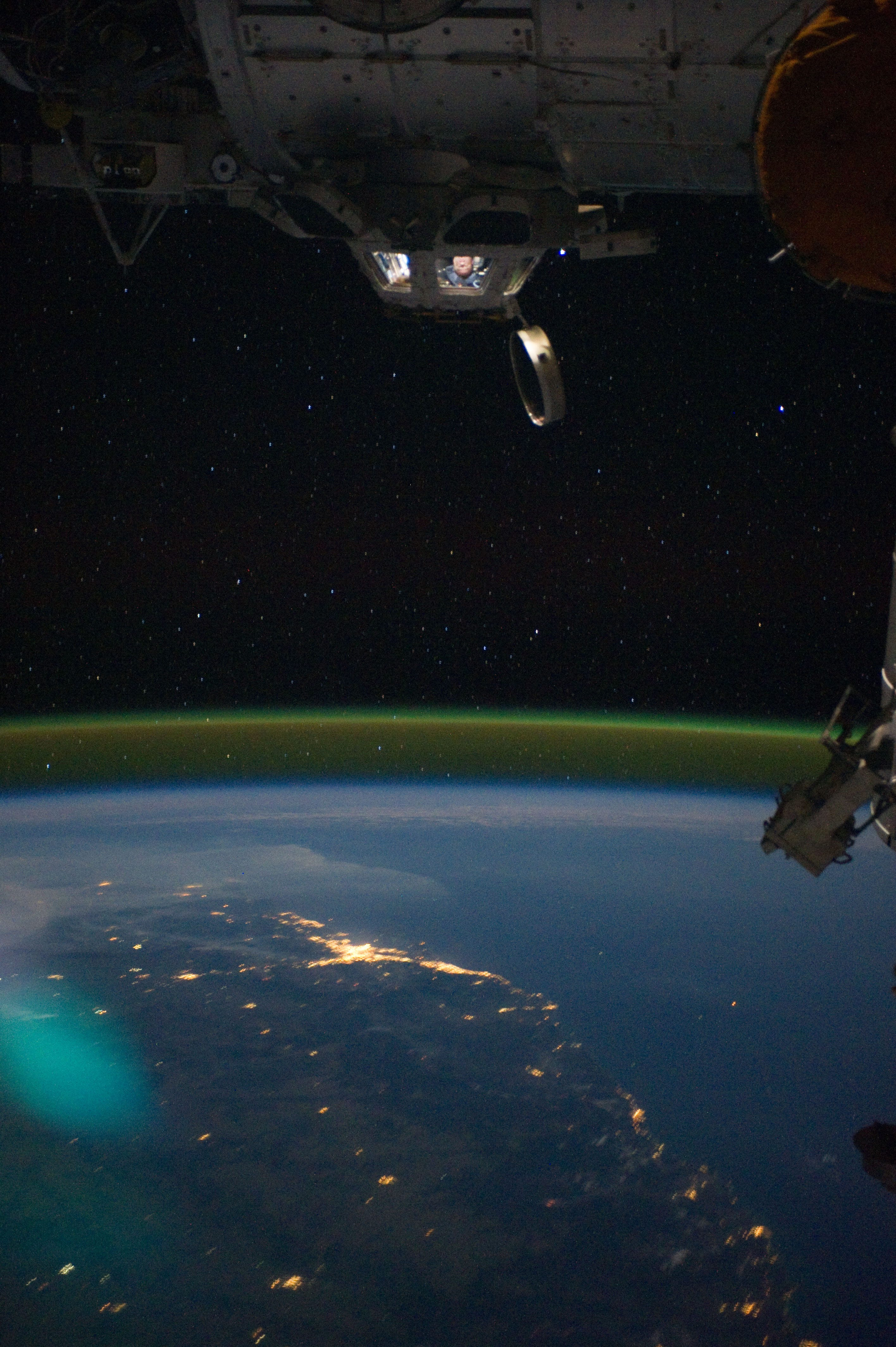 """View of the International Space Station orbiting over Australia The photograph clearly captures the shimmer of """"airglow"""" in the earth's upper atmosphere. The phenomena is rarely seen from the planet's surface, but is clearly visible from space. Note the astronaut in the space stations cupola."""