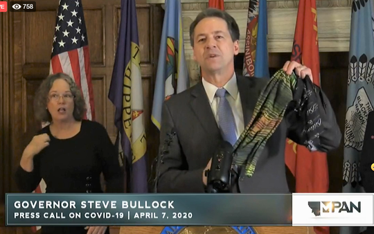 Gov. Steve Bullock holds up a cloth mask Tuesday as he extends the stay-at-home directive. Victoria Gregori, a sign language interpreter, stands behind him.