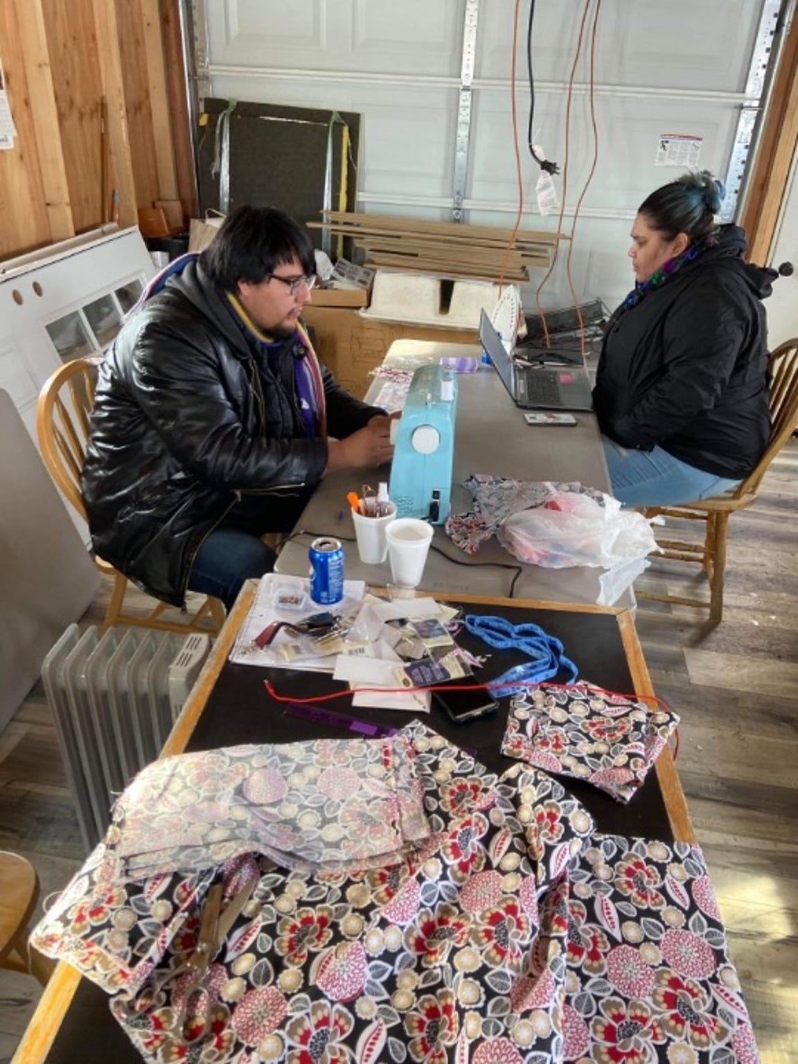 Millie Bearleggings works with a volunteer to sew masks for members of the Blackfeet Nation.