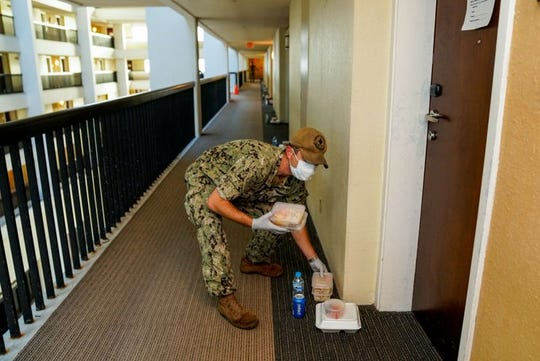 A sailor delivers food to hotel rooms designated for sailors assigned to the USS Theodore Roosevelt who were moved to local hotels on Guam as part of an aggressive mitigation strategy to minimize the spread of COVID-19.