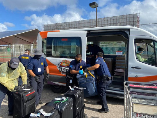 Commonwealth of the Northern Mariana Islands officials process the last passenger flight from United Airlines which arrived on Saipan on April 5, 2020. The flight was the last service to enter the CNMI until further notice.
