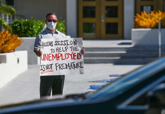 Sen. James Moylan displays a sign to a passing motorist at a peaceful protest held in front of the Guam Congress Building in Hagåtña on Tuesday, April 7, 2020. Moylan said the protest was held in hopes of encouraging other fellow lawmakers to convene for a legislative session to address the needs of island residents, especially those now unemployed by the coronavirus, or COVID-19, pandemic.