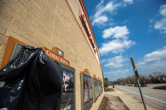 A trash bag covers a movie poster display at a Marcus Theatre, Tuesday, April 7, 2020, at Coral Ridge Mall in Coralville, Iowa. Malls across the state were ordered to close by Iowa Gov. Kim Reynolds to combat the spread of COVID-19.