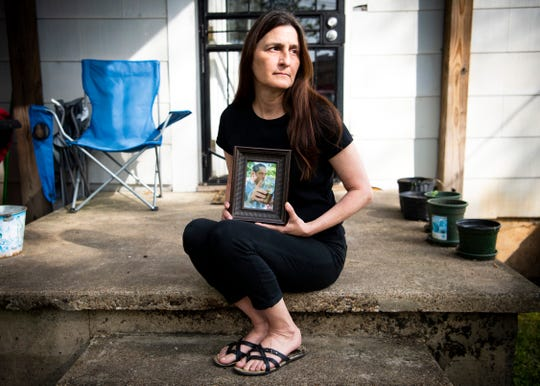 Knoxville bartender Corrina Perkins is photographed on her porch with a photograph of her late husband Patrick Perkins on Tuesday, April 7, 2020. Corrina's husband Patrick passed away March 8, 2020, and when Corrina returned to work a week later, the restaurant she worked at shut down because of the coronavirus.