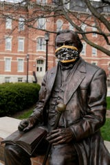 A statue of John Purdue, the founder of Purdue University, is seen wearing a Purdue surgical mask, Tuesday, April 7, 2020 in West Lafayette.