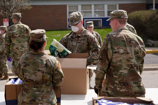 Members of the Indiana National Guard load cars with food items at a drive-thru pantry for Food Finders Food Bank outside of Linwood Elementary School, April 7, 2020, in Lafayette. Hundreds of members will be deployed in the coming weeks to nursing homes across the state to help combat the coronavirus.