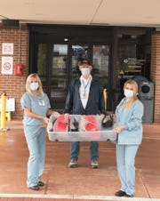 St. Joseph Mercy Livingston Hospital nurses Kim Bannon, left, and Kelly Derby hold a bin of face shields donated by Michael Peddie, center, president of the Howell Gun Club Tuesday, April 7, 2020. A number of members of the gun club who own 3D printers produced the shields for the hospital staff to use when caring for patients who may be carrying the COVID-19 virus.