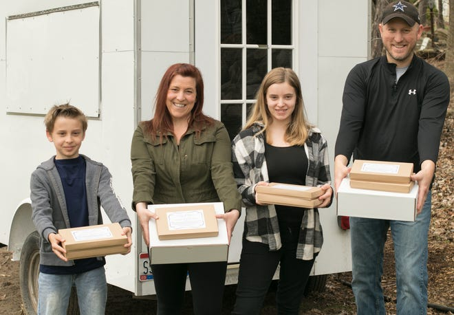 Keri Hayes and her husband Greg, with their children 11-year-old Quinn and Avery, 14, hold boxes of Whey Better Bakery protein peanut butter cups Tuesday, April 7, 2020. The Hayeses are selling the peanut butter cups through Home Shopping Network.
