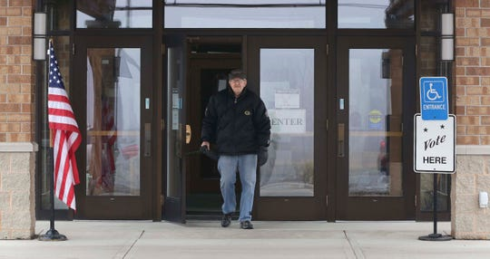 Paul Koch, of Two Rivers, walks out of the Grace Church poll after voting, Tuesday, April 7, 2020, in Two Rivers, Wis.