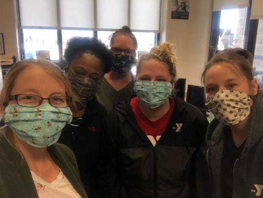 Child care staff at the Mansfield Area Y don their masks.