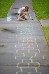Ellie Spillyards, 11, draws hopscotch squares in chalk on the sidewalk Tuesday, April 7, 2020, on Melody Lane in Memphis. Spillyards has been using her newfound downtime to train to break the hopscotch world record.