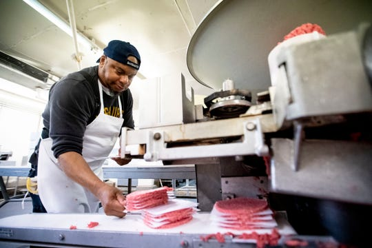 Dewayne Rhodes pulls stacks of ten quarter pound hamburger patties off a patty machine Tuesday, April 7, 2020, at Charlie's Meat Market in Memphis. Co-owner Chuck Hogan said the store has seen at least a 30 percent bump in business in recent weeks.