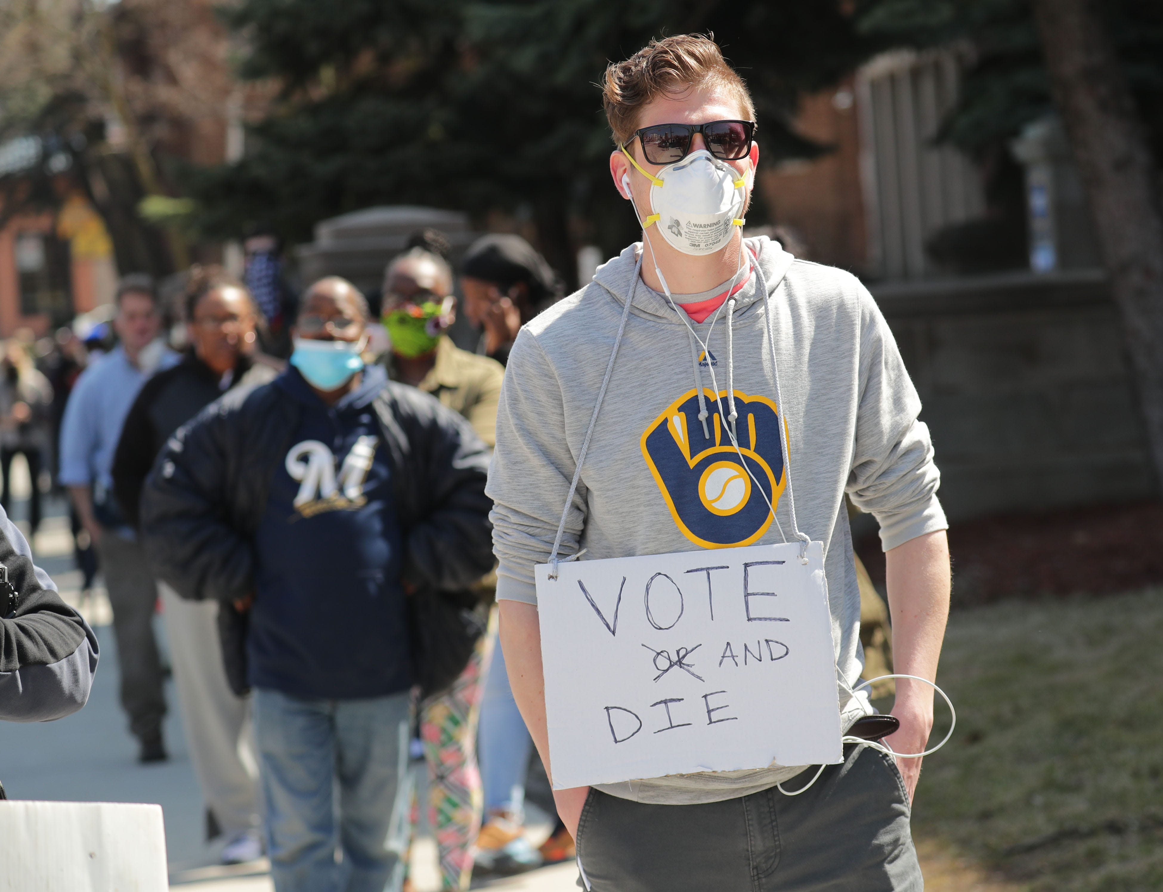 Torin Fendos, of Milwaukee, wears a sign voicing his view while waiting to vote at Riverside High School, 1615 E. Locust St. in Milwaukee on Tuesday, April 7, 2020. The Wisconsin primary is moving forward despite the coronavirus epidemic after Gov. Tony Evers sought to shut down Tuesday's election in a historic move Monday that was swiftly rejected by the conservative majority of the Wisconsin Supreme Court.