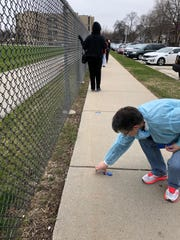 A worker at Washington High School in Milwaukee lays down tape to indicate 6 feet of distance for voters in line April 7, 2020.