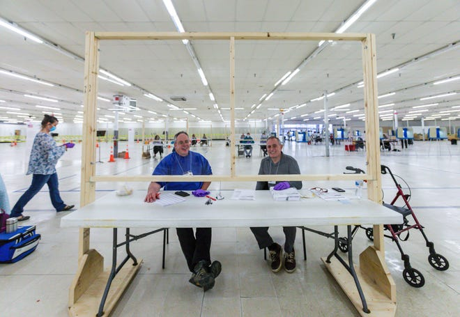 City of Oconomowoc poll workers Robert Kolb (left) and Nick Argeroudis sit behind a plexiglass panel as they wait to assist voters on Tuesday, April 7, 2020. The polling station, inside the former Kmart building, had moderate traffic.