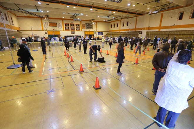 People wait to register and vote at Riverside High School, 1615 E. Locust St. in Milwaukee on Tuesday, April 7, 2020.