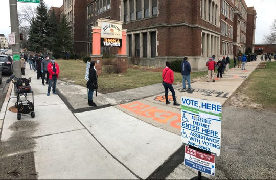 Voters circle around the block on Locust Street and keep a safe distance from each other at Riverside University High School in Milwaukee during election day April 7, 2020.