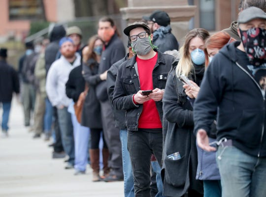 People line up to vote at Riverside High School in Milwaukee on Tuesday. The Wisconsin primary is moving forward despite the coronavirus epidemic after Gov. Tony Evers sought to shut down Tuesday's election in a historic move Monday that was swiftly rejected by the conservative majority of the Wisconsin Supreme Court.