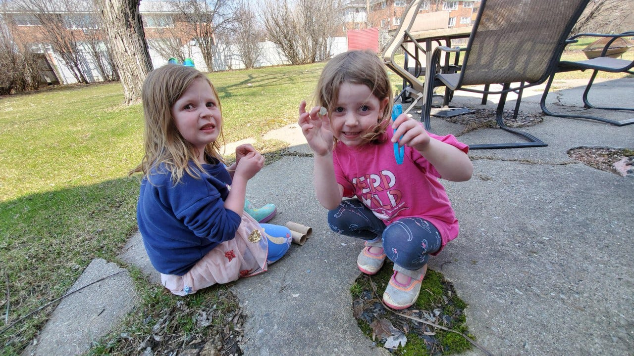 Annie and Lucy Fladten play in their yard. Their mom and dad are juggling working at home with serving as their daughters' teachers.