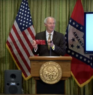Gov. Asa Hutchinson holds an Arkansas Razorback-themed face mask that he wore to Tuesday's COVID-19 news conference. The governor said he was open to wearing other Arkansas university-themed masks as they became available to him.