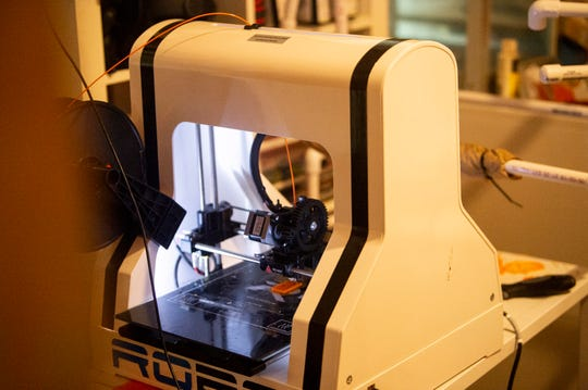 Joe Birdwell makes tools to help make homemade face masks on his 3D printer at his home in Montgomery, Ala., on Tuesday, April 7, 2020.