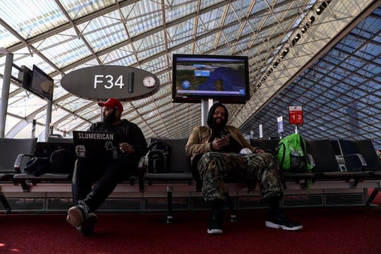 Bray, left, and Big Henri sit in the almost empty airport in Amsterdam on March 31, 2020.