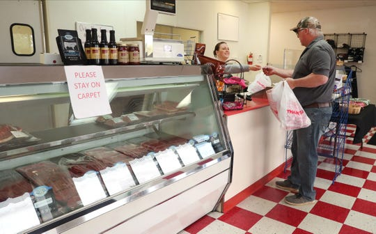 Denise Malone, left, checks out customer Jim Stacey, right, at Tag'z 5 Star Meats, in Murfreesboro, Tenn., on Tuesday, April 7, 2020.
