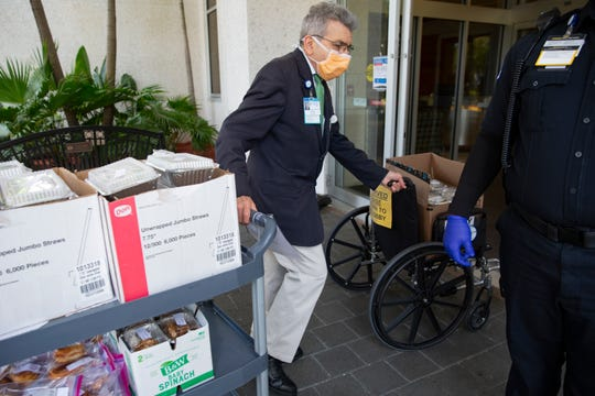 Peter Fisfis, concierge at Naples Community Hospital Baker, brings in donated meals for the hospital staff, Tuesday, April 7, 2020, at NCH Baker in Naples.