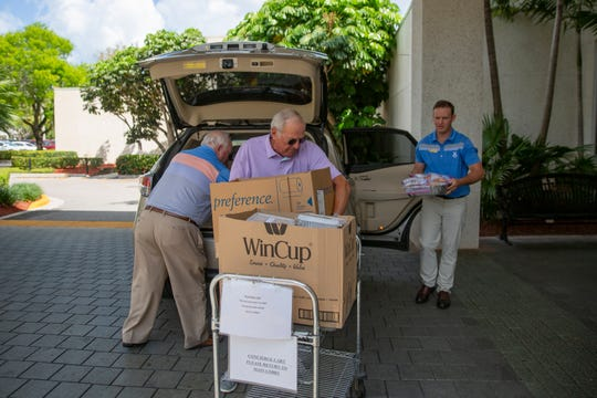 Moorings Golf and Country Club members Ted Beisler, left, member Walter Putis, center, and Chris Rockwell unload 100 meals for the staff at NCH Baker in Naples on Tuesday, April 7, 2020.