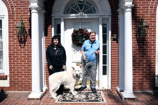 Phyllis and Rene Supino pose with their dog, Hero, in front of their Westwood home on Tuesday, April 7, 2020. Their neighbors answered a Facebook plea from their daughter, Lisa, in Georgia, and offered to do the couple's grocery shopping and to walk Hero.