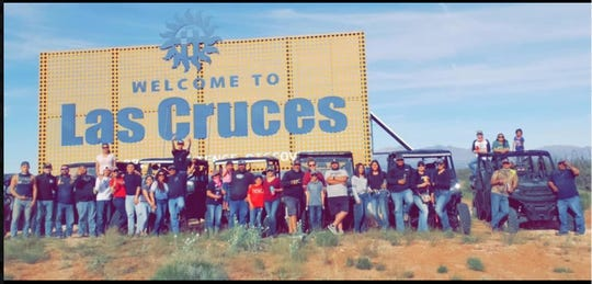 "A group photograph posted to social media on Sunday, April 5, 2020, shows a gathering by the Interstate 10 ""Welcome to Las Cruces"" sign, in defiance of state health department orders to limit social gatherings to five people or less and limit travel. One of the hashtags on the Facebook post was #IfIGotItYouGotIt - ""If I got it, you got it."""