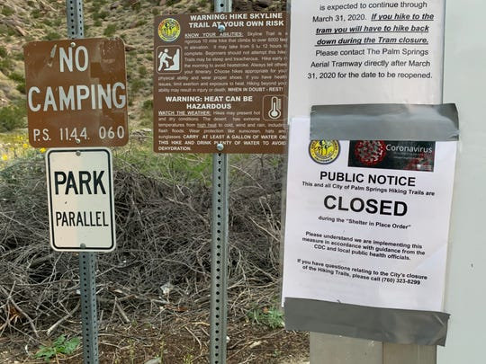 A sign advises people that Palm Springs' North Lykken trail is closed to the public Tuesday, April 7, 2020. City staff says the signs were accidentally posted and trails are still open to the public, but parking is no longer allowed at trailheads to help prevent the spread of coronavirus.