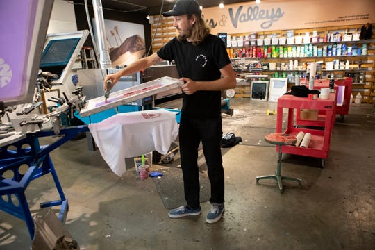 Glen Coy screen prints a t-shirt which is being used for the #KeepShiningPSP fundraiser to support local businesses and hospitality workers, inside Windmill City Screen Printing shop in Cathedral City, Calif., on April 7, 2020.