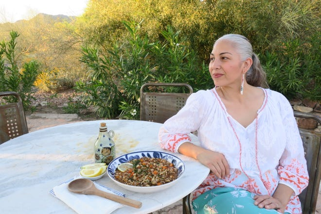 Phoenix healer Felicia Cocotzin Ruiz sits on her back patio with a bowl of black eyed peas cooked with onion, carrots and herbs and featuring fresh lemon juice.