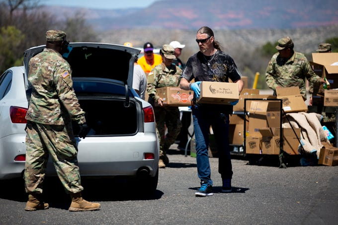 Army national guard members and volunteers pass out food and supplies at Project Rising Hope Food Pantry in Cottonwood, Ariz. on April 7, 2020.