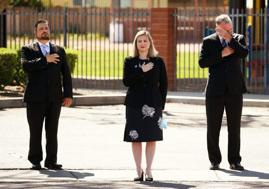 Councilmember Michael Nowakowski, Mayor Kate Gallego and City Manager Ed Zuercher (right) react as the casket of Phoenix Police Commander Greg Carnicle arrives for his funeral mass at Saint Jerome Catholic Church in Phoenix.