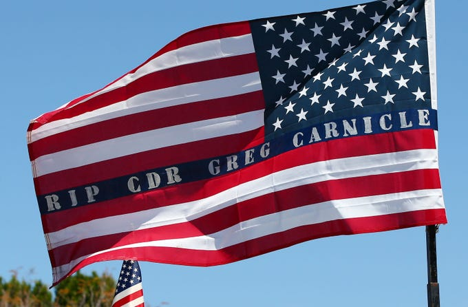 Apr. 7, 2020; Phoenix, AZ, USA; A U.S. flag carries a message for Phoenix Police Commander Greg Carnicle during his funeral mass at Saint Jerome Catholic Church in Phoenix. Commander Greg Carnicle was a 31-year veteran who was shot and killed on duty. Mandatory Credit: Rob Schumacher/The Arizona Republic via USA TODAY NETWORK