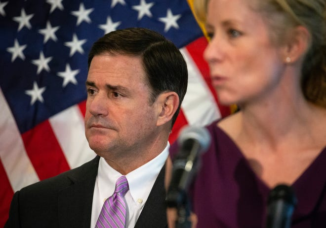 Gov. Doug Ducey listens (left), while Dr. Cara Christ (right) answers a question, April 7, 2020, during a COVID-19 news conference at the Arizona Commerce Authority Conference Center in Phoenix.