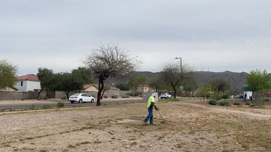 A landscaper battles weeds in a Phoenix lot.
