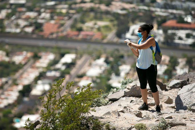 Wearing a mask and gloves because of the coronavirus pandemic, Melanie Alston of Phoenix, takes a rest while  hiking the trail up Piestewa Peak in the Phoenix Mountains Preserve on April 6, 2020.