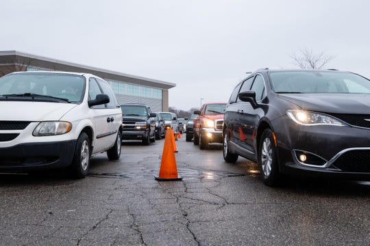 Vehicles line up at Marysville High School Tuesday, April 7, 2020, to receive five days' worth of meals. To minimize contact, food workers and volunteers from the district would set out the required number of meals on a table near the vehicles, and family members would pick them up and take them back to their car.