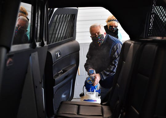 Jane Bailey assists as driver John Patterson, of Bailey Coach, disinfects a York County Sheriff vehicle free of charge on the first day of offering this service free to York County first responders at Bailey Coach in Jackson Township, Tuesday, April 7, 2020. Dawn J. Sagert photo